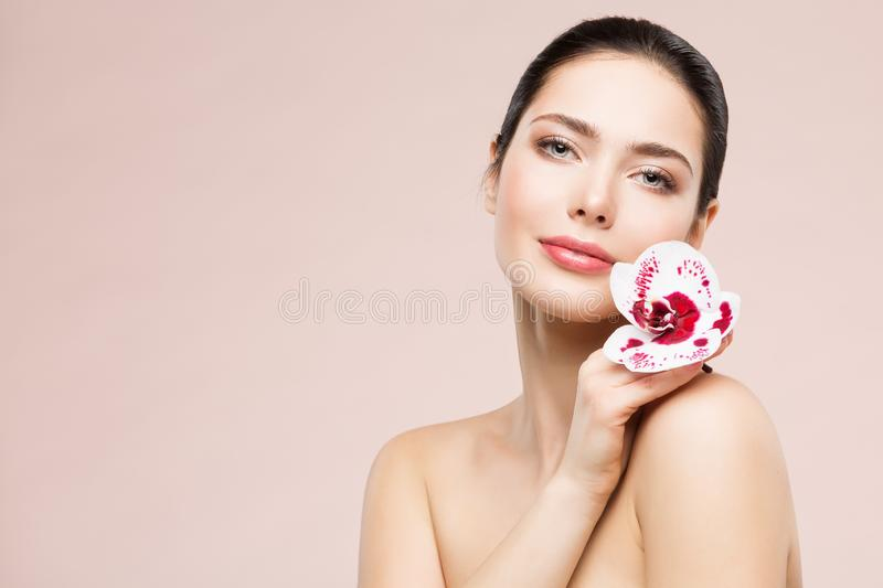 Woman Natural Beauty Makeup Portrait with Orchid Flower, Beautiful Girl Skin Care and Treatment. Shot over beige studio background royalty free stock photo