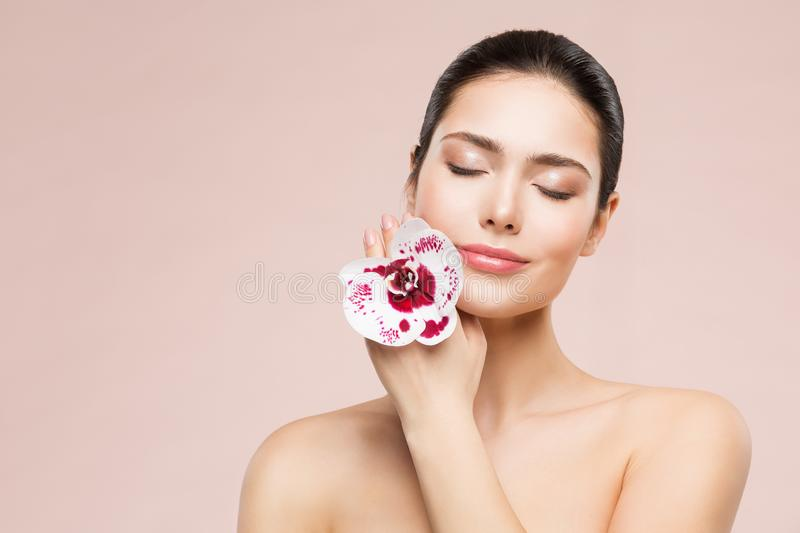 Woman Natural Beauty Makeup Portrait and Orchid Flower, Happy Girl Dreaming Skin Care and Treatment. Shot over beige studio background stock photography