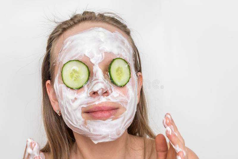 Woman with natural cream mask and cucumbers on her face royalty free stock images