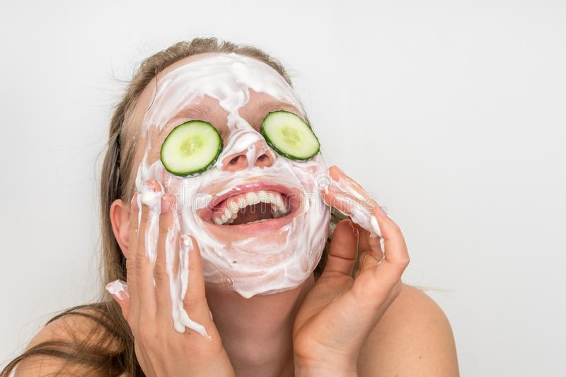 Woman with natural cream mask and cucumbers on her face stock photos
