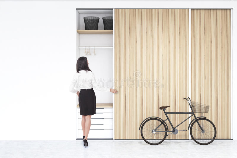 Woman near a built in wadrobe in a room with bike stock images