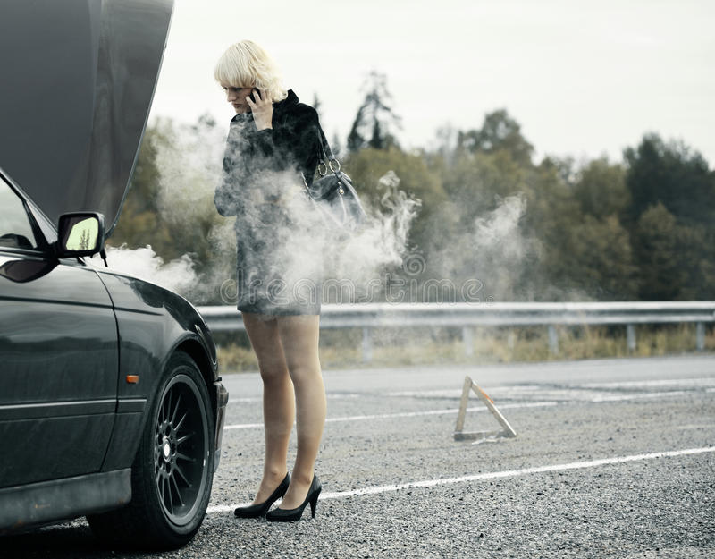 Woman near car. Young woman talking on mobile phone near broken and smoking car royalty free stock image