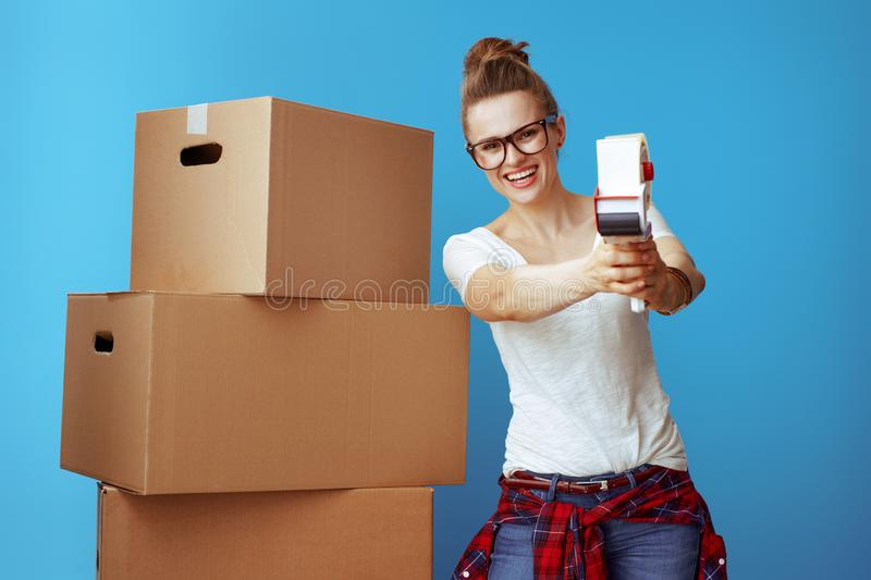 Woman near cardboard box using with tape dispenser as a gun stock image
