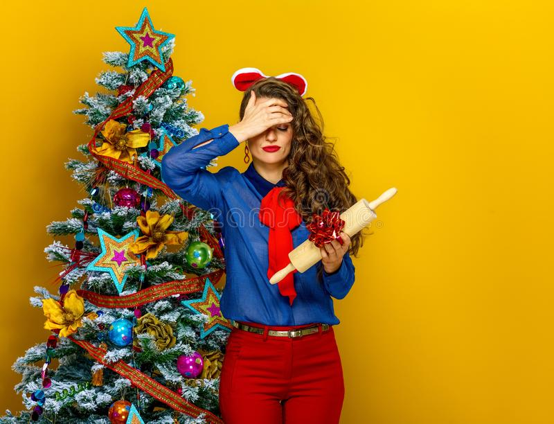 Woman near Christmas tree holding unwanted present. Festive season. unhappy young woman near Christmas tree on yellow background holding unwanted present stock images