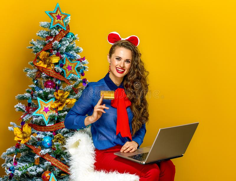 Woman near Christmas tree with laptop showing credit card. Festive season. happy elegant woman near Christmas tree on yellow background with laptop showing royalty free stock photos