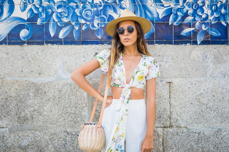 Elegant woman near city wall wearing sunglasses and white t-shirt at hot summer day in the city royalty free stock photography
