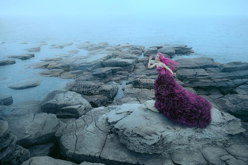 Woman near foggy sea. Woman in Purple Dress Looking to Mountains Sea stock image