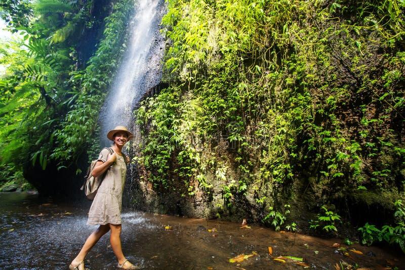 Woman near waterfal on Bali, Indonesia royalty free stock image