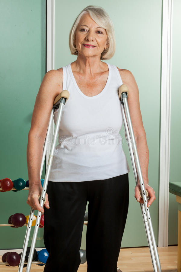 Woman with a neck brace using crutches. Old woman with a neck brace using crutches royalty free stock photo