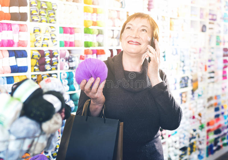 Woman with needlework accessories and talking on phone royalty free stock image