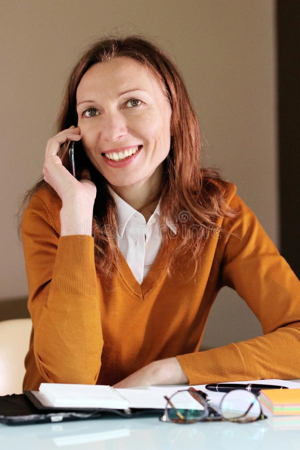 Woman negotiating with the client over the phone stock photos