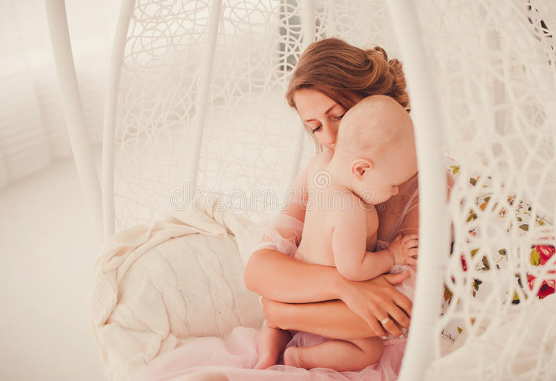 Woman and new born boy. Young mother hugging her newborn child. Woman and new born boy sitting in a white chair royalty free stock image