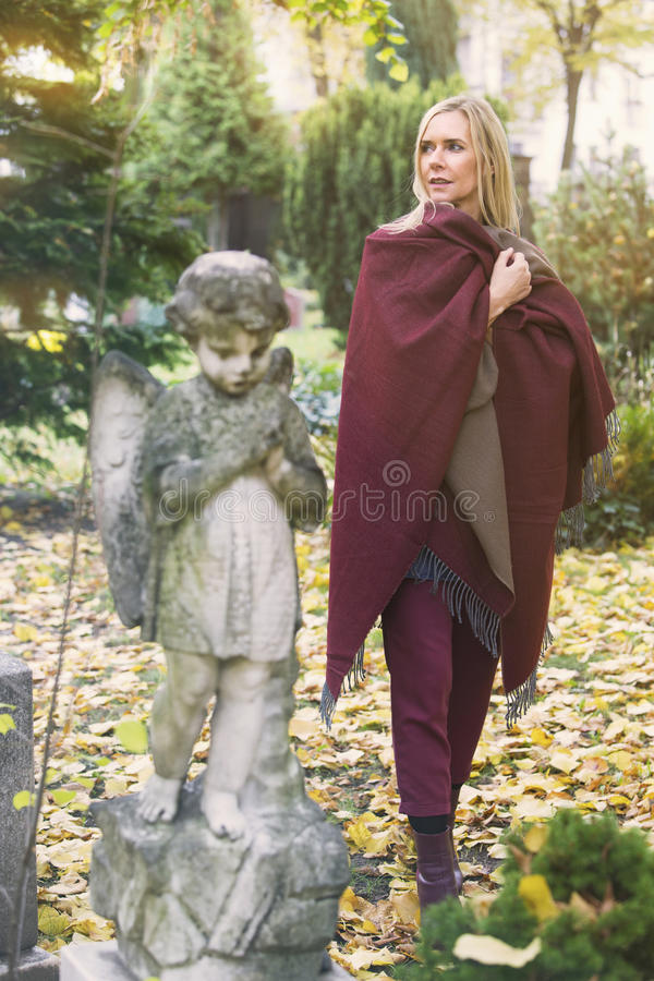 Woman next to a grave with an angel royalty free stock image
