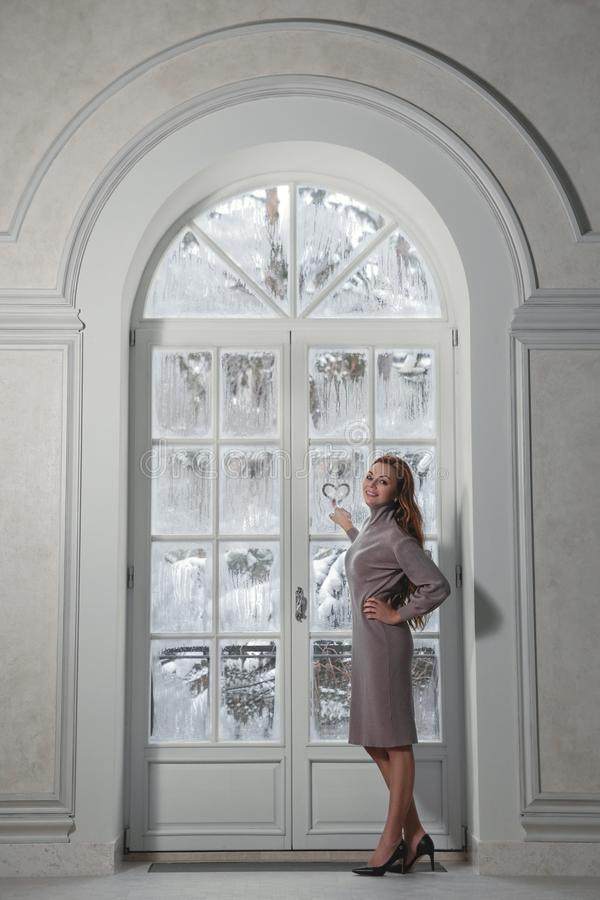 Woman next to winter window royalty free stock photo