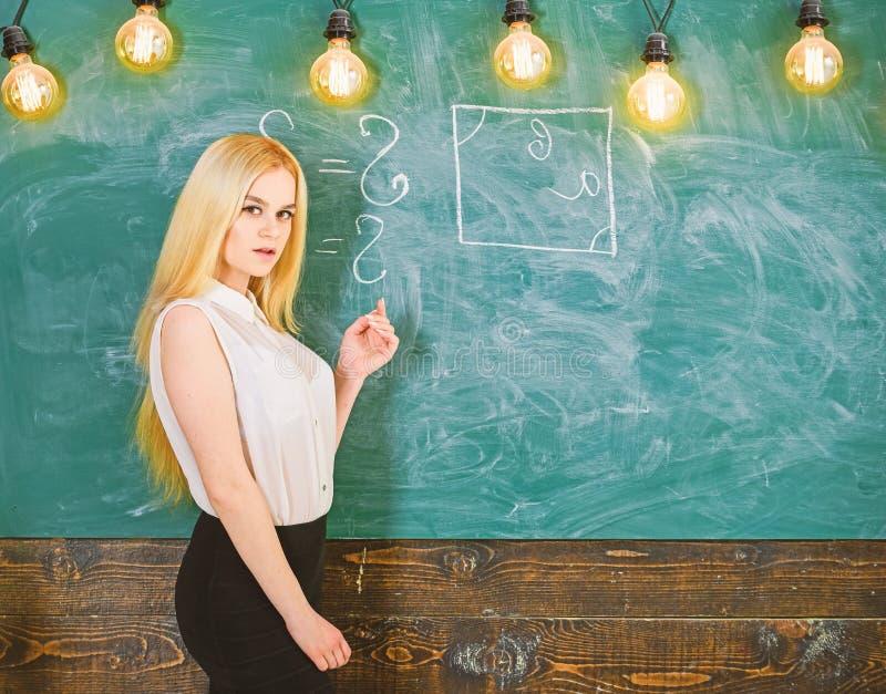 Woman with nice buttocks teaching mathematics. teacher concept. Lady teacher with long hair explaining formula. Teacher of mathematics writing on chalkboard stock images
