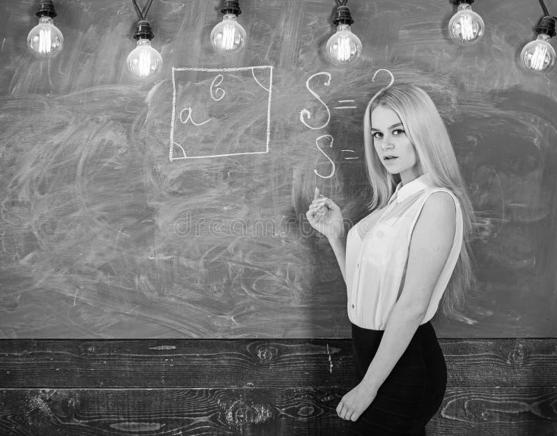 Woman with nice buttocks teaching mathematics. teacher concept. Lady teacher with long hair explaining formula. Teacher of mathematics writing on chalkboard stock photo