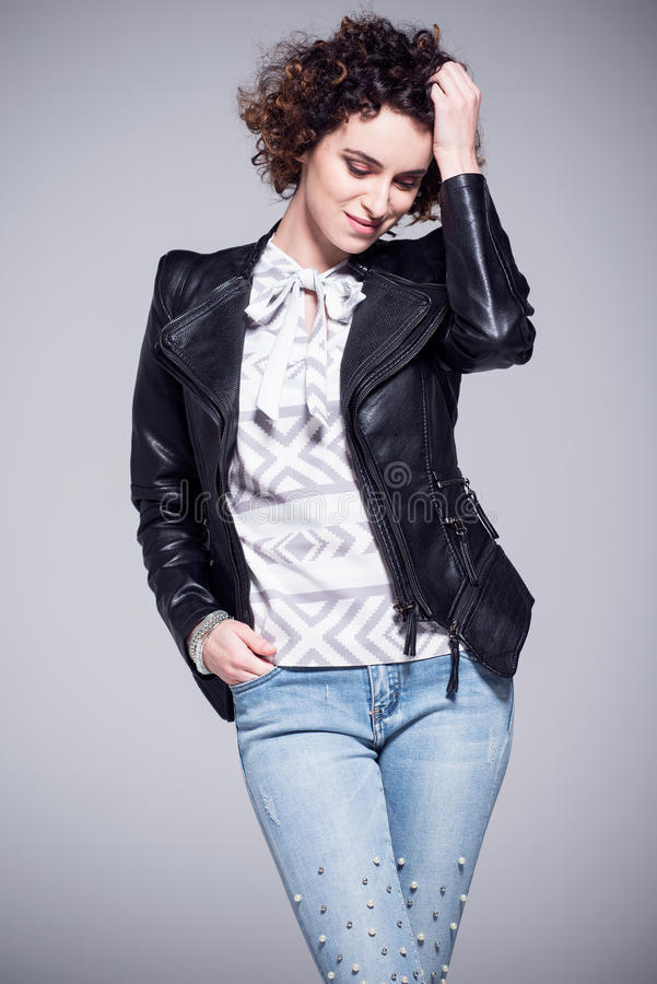 Woman with nice smile and afro hairstyle, dressed in black leather jacket stock image