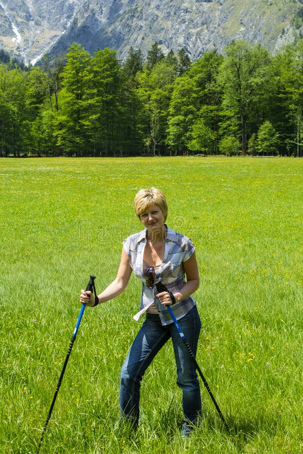 a woman with nordic walking sticks with mountains in the background is taking a break royalty free stock images