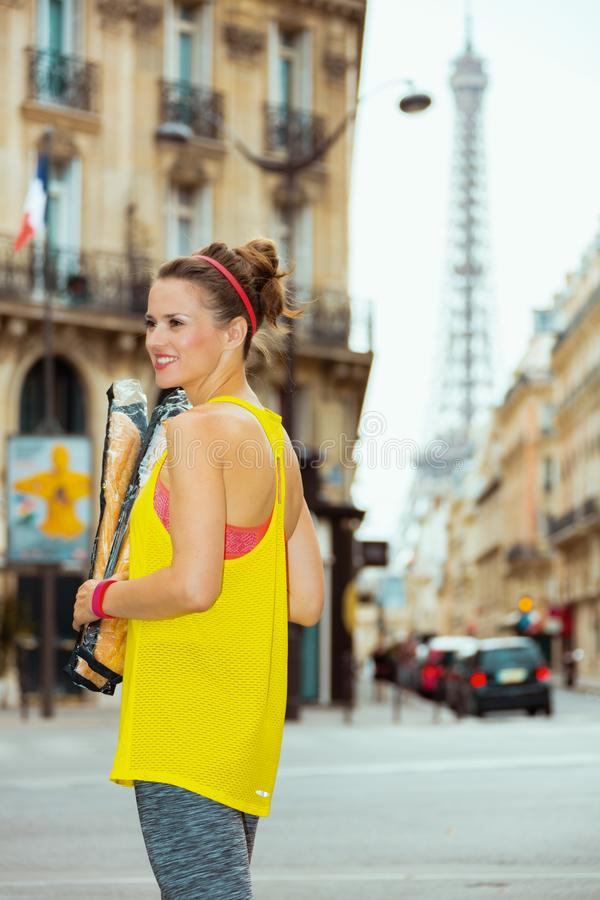 Woman not far from Eiffel tower with French baguettes. Smiling active woman in fitness clothes with French baguettes not far from Eiffel tower in Paris, France stock image