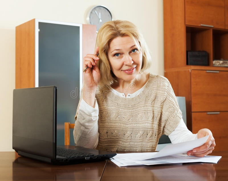 Woman with notebook and financial documents in office. Serious mature woman with notebook and financial documents at table in office royalty free stock photos