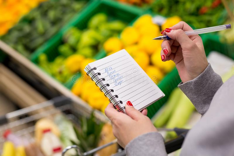 Woman with notebook in grocery store, closeup. Shopping list on paper. royalty free stock images