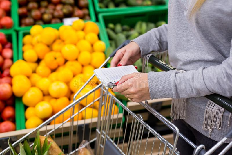 Woman with notebook in grocery store, closeup. Shopping list on paper. Woman with notebook in grocery store, closeup. Shopping list on paper stock image
