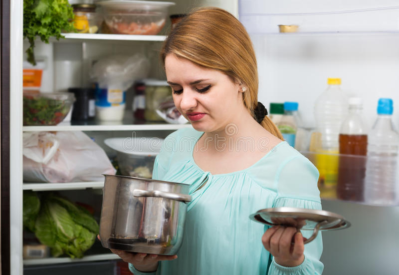 Woman noticed foul smell of food from casserole. Long-haired spanish woman noticed foul smell of food from casserole stock images
