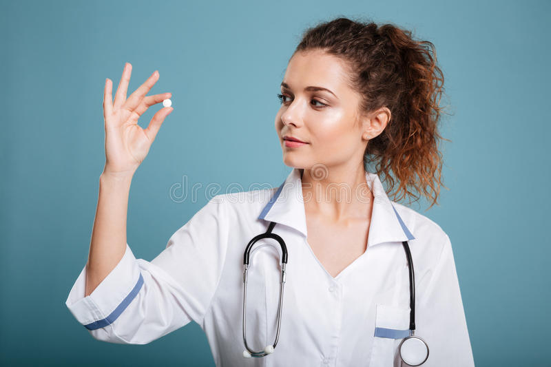 Woman nurse looking at pill in her fingers. Young nurse wearing lab coat looking at pill in hand isolated over blue background stock photos