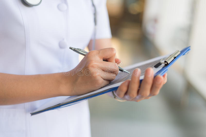 Woman nurse in white coat reports in a notebook. Image of woman nurse in white coat reports in a notebook royalty free stock photos