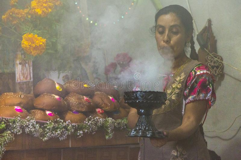Calling the Dead. A woman in Oaxaca, Mexico blows on incense to summon sports of her ancestors during Day of the Dead celebrations stock photo
