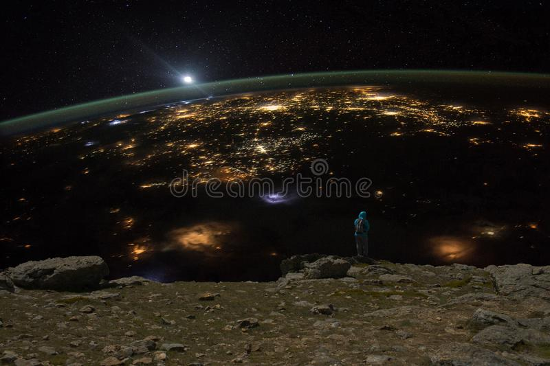 Woman observing the earth from an imaginary cliff during the night stock photography