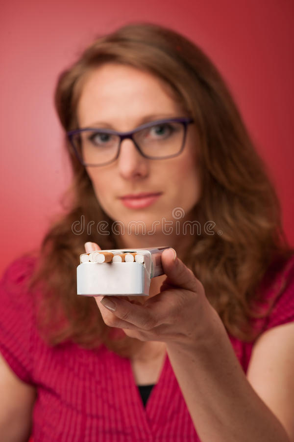 Woman offering a cigarette. Beautiful young woman offering a cigarette, unhealthy habit stock photo