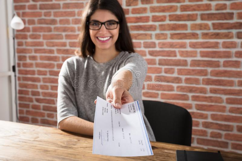 Woman Offering Company Cheque. Smiling Young Woman Offering Company Cheque At Workplace stock images