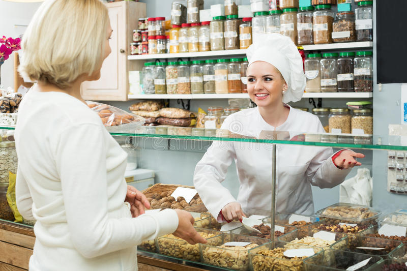 Woman offering female client nuts. Cheerful shop women offering female client nuts and smiling stock photography