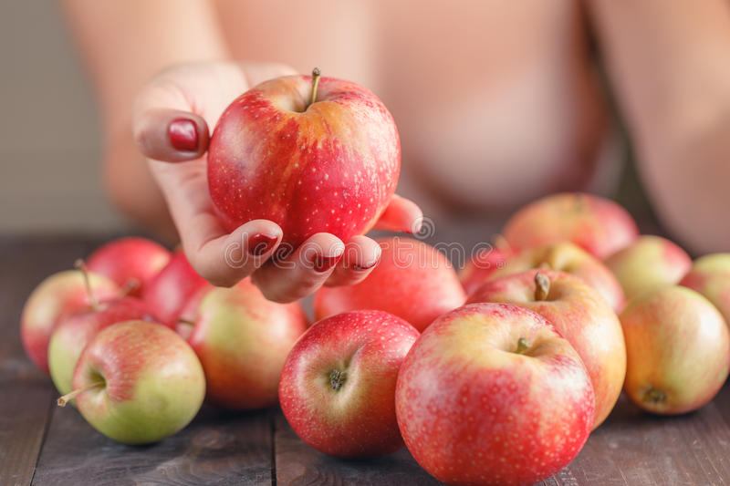 Woman offering red apple, shallow DOF, Focus on the apple royalty free stock photography