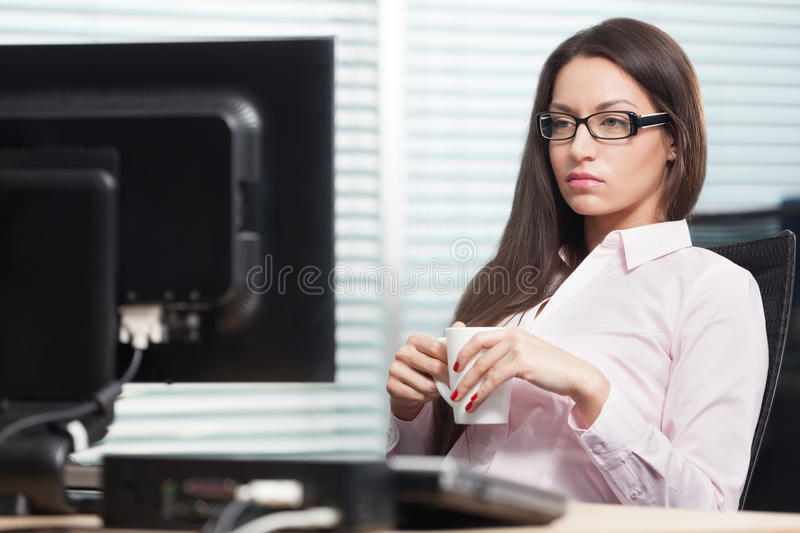 Woman at office. Beautiful and smart woman sitting at office with cup of tea royalty free stock photo