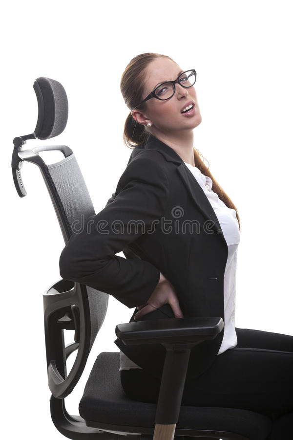 Woman in office chair. Woman with backpain sits on office chair holding her hand on back royalty free stock photos