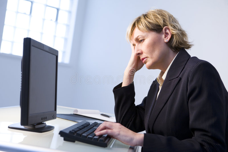 Woman in office on computer. Weary middle-aged woman sitting at computer in office stock image