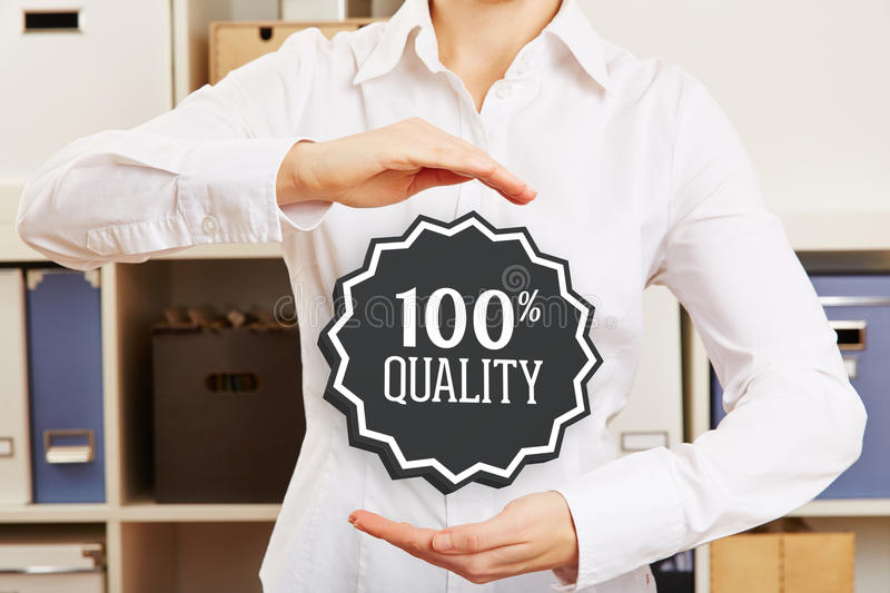 Woman in office guaranteeing 100% quality. Business woman in office guaranteeing 100% quality with a hovering badge royalty free stock photo