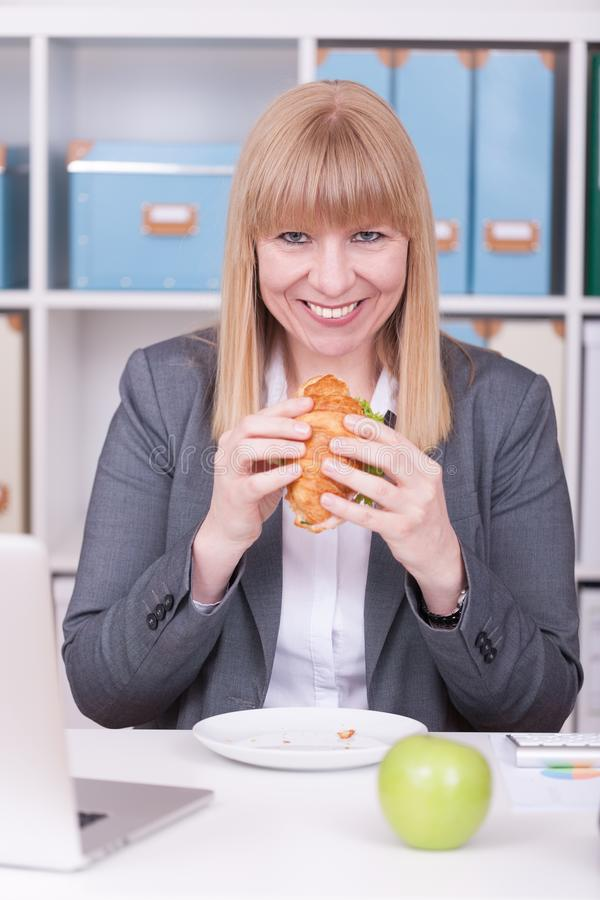 Woman at the office having lunch. Concept for healty or unhealthy food at work stock photography