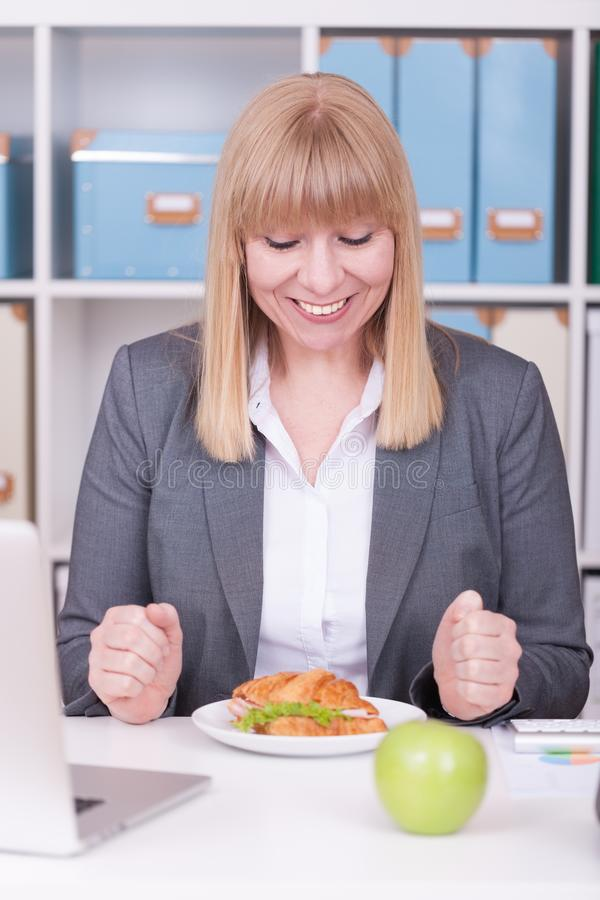 Woman at the office having lunch. Concept for healty or unhealthy food at work stock photo