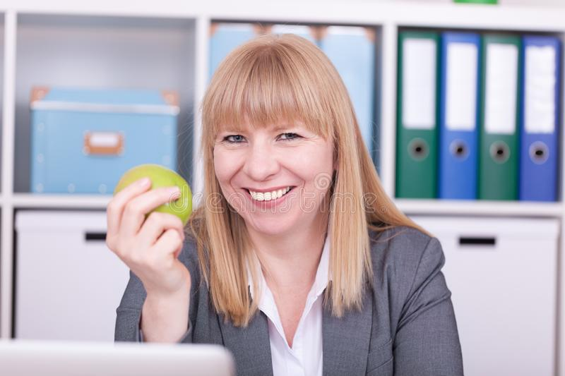 Woman at the office having lunch. Concept for healty or unhealthy food at work royalty free stock images