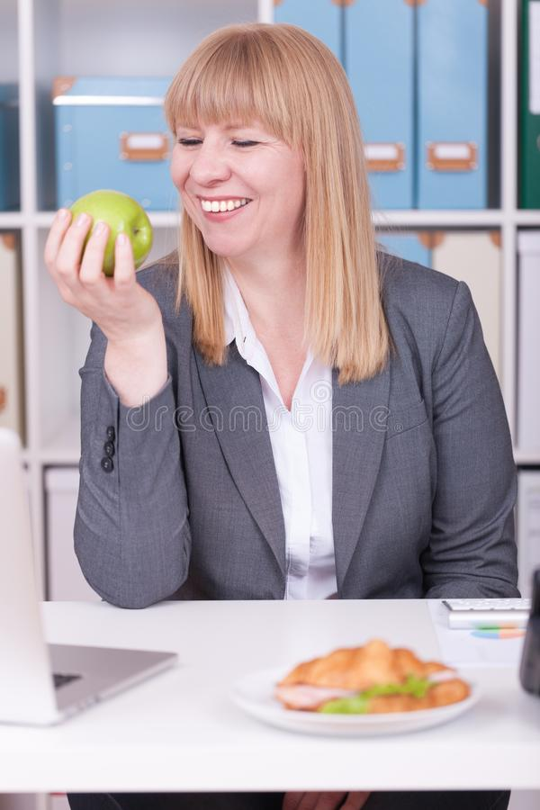 Woman at the office having lunch. Concept for healty or unhealthy food at work royalty free stock image