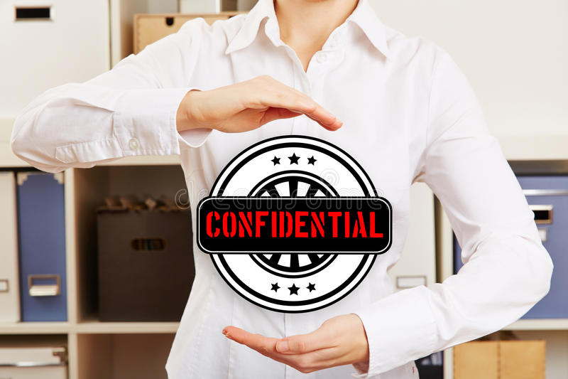 Woman in office holding confidential badge. Business woman in office holding a hovering confidential badge between her hands stock images