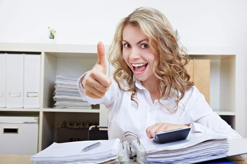 Woman in office holding thumbs up stock image