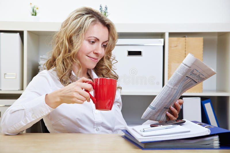 Download Woman In Office Reading Newspaper Stock Image - Image: 25975965