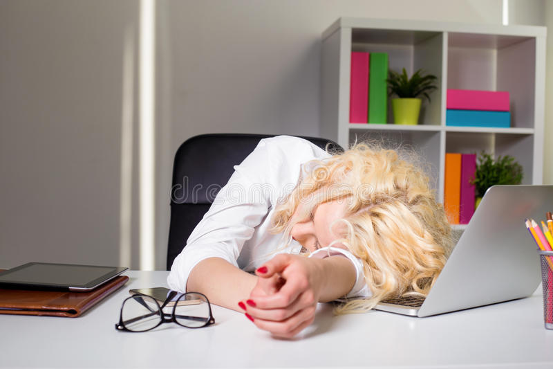 Woman at the office sleaping on the table royalty free stock photos