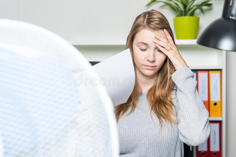 Woman in the office suffers from the heat and using a ventilator for cooling stock photos