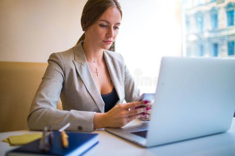 Woman office worker using apps on cellphone during online education via netbook device stock photography