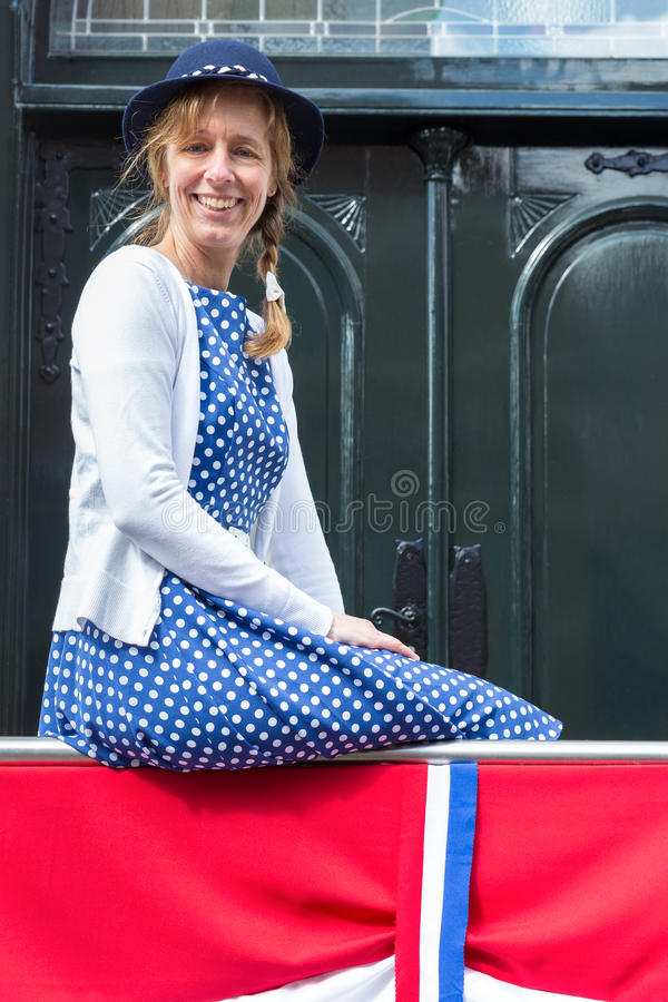 Woman in old-fashioned clothes with dutch flag. Caucasian middle aged woman in old-fashioned clothes with dutch flag. The european woman wears a blue dress and stock photo